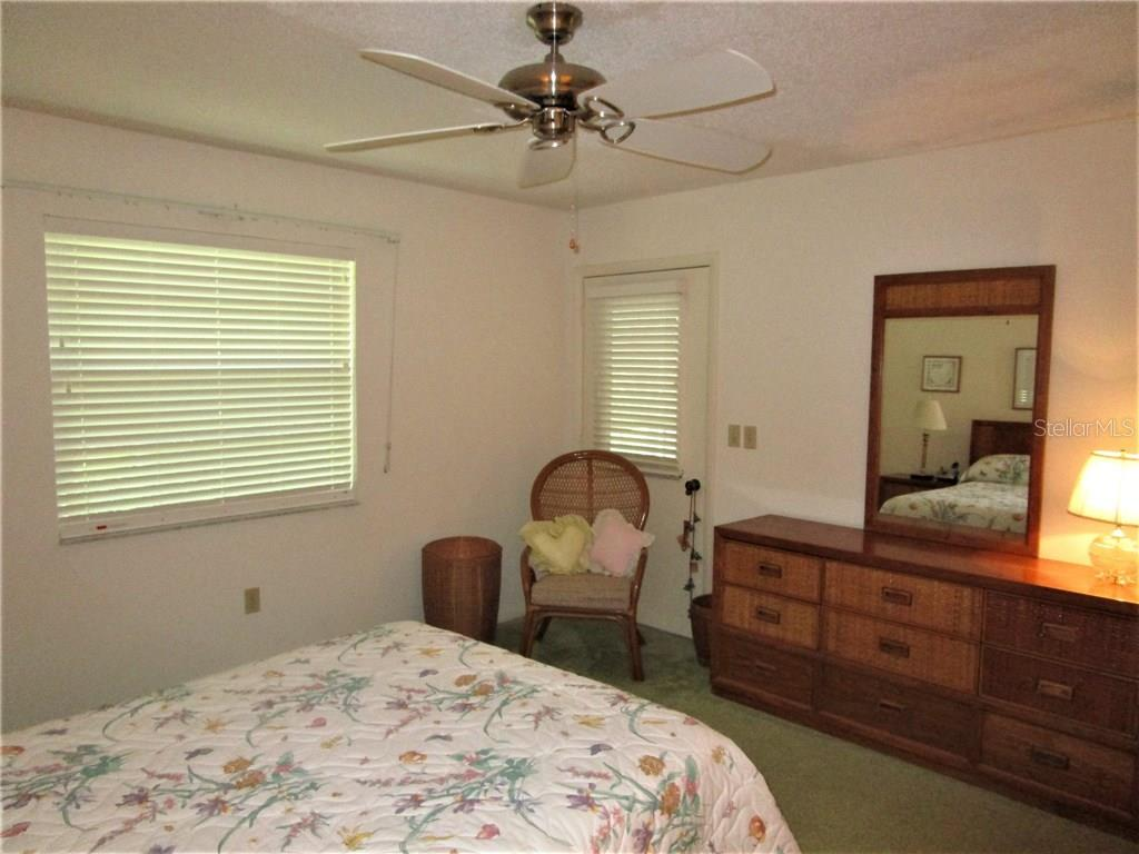 Master bedroom has ceiling fan, carpeted flooring & door to Lanai. - Condo for sale at 6796 Gasparilla Pines Blvd #14, Englewood, FL 34224 - MLS Number is D5919892