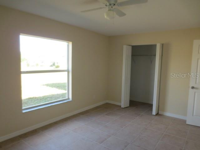 Front guest bedroom has tiled flooring, ceiling fan and wall closet. - Single Family Home for sale at 7385 Teaberry St, Englewood, FL 34224 - MLS Number is D6101274