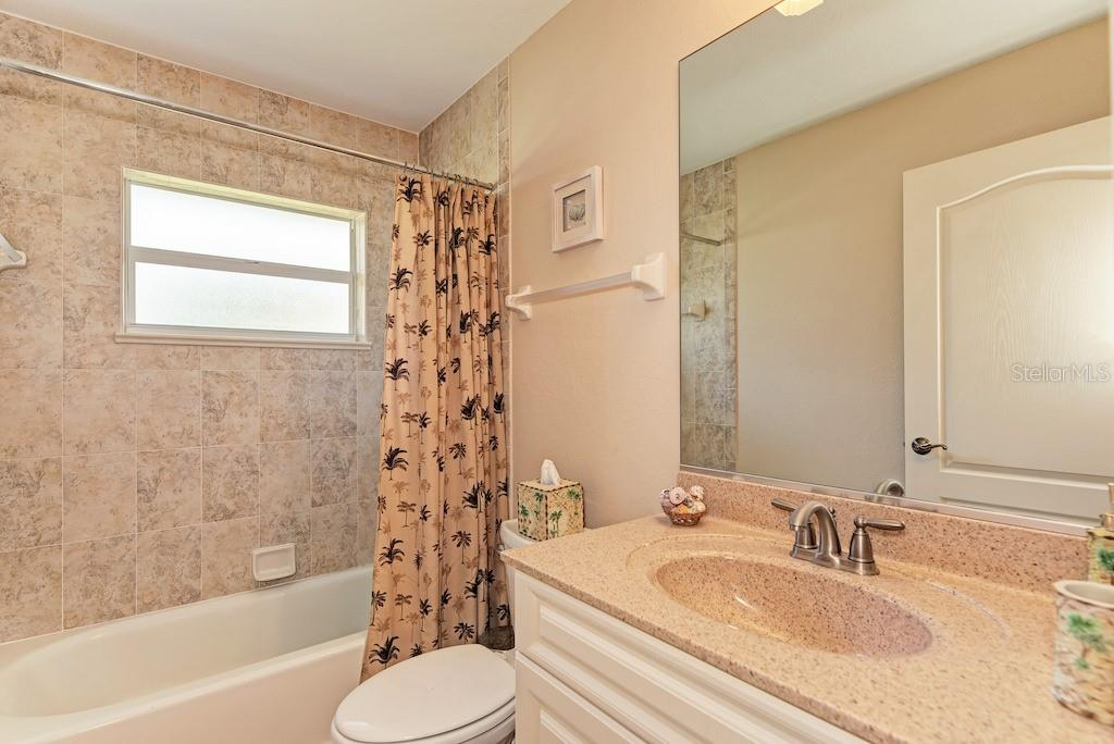 Guest bathroom with tub and shower in between guest bedrooms. - Single Family Home for sale at 7256 Holsum St, Englewood, FL 34224 - MLS Number is D6101787