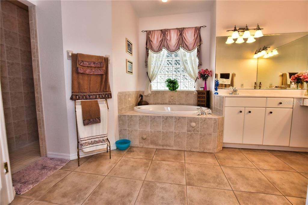 Master Bathroom, walk in shower, garden tub, dual sinks, private loo and Jack n Jill walk in closet. - Single Family Home for sale at 8 Medalist Cir, Rotonda West, FL 33947 - MLS Number is D6104474