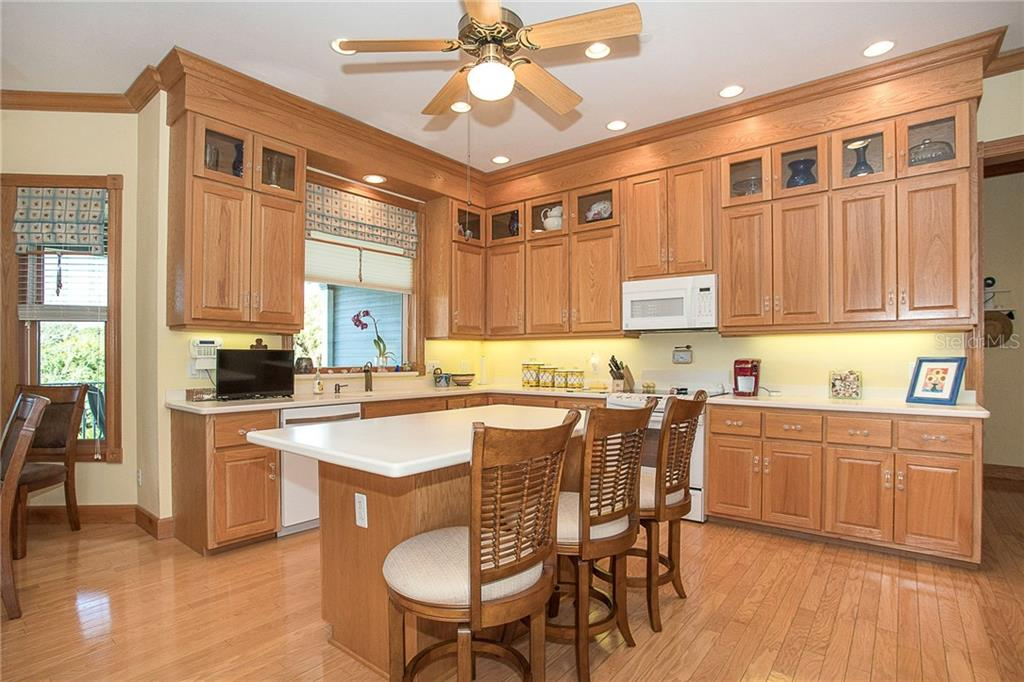 This cook's kitchen offers a large island, custom wood cabinetry, casual dining nook, fireplace and huge walk-in pantry. You need to see it in person to take it all in! - Single Family Home for sale at 550 S Oxford Dr, Englewood, FL 34223 - MLS Number is D6111512