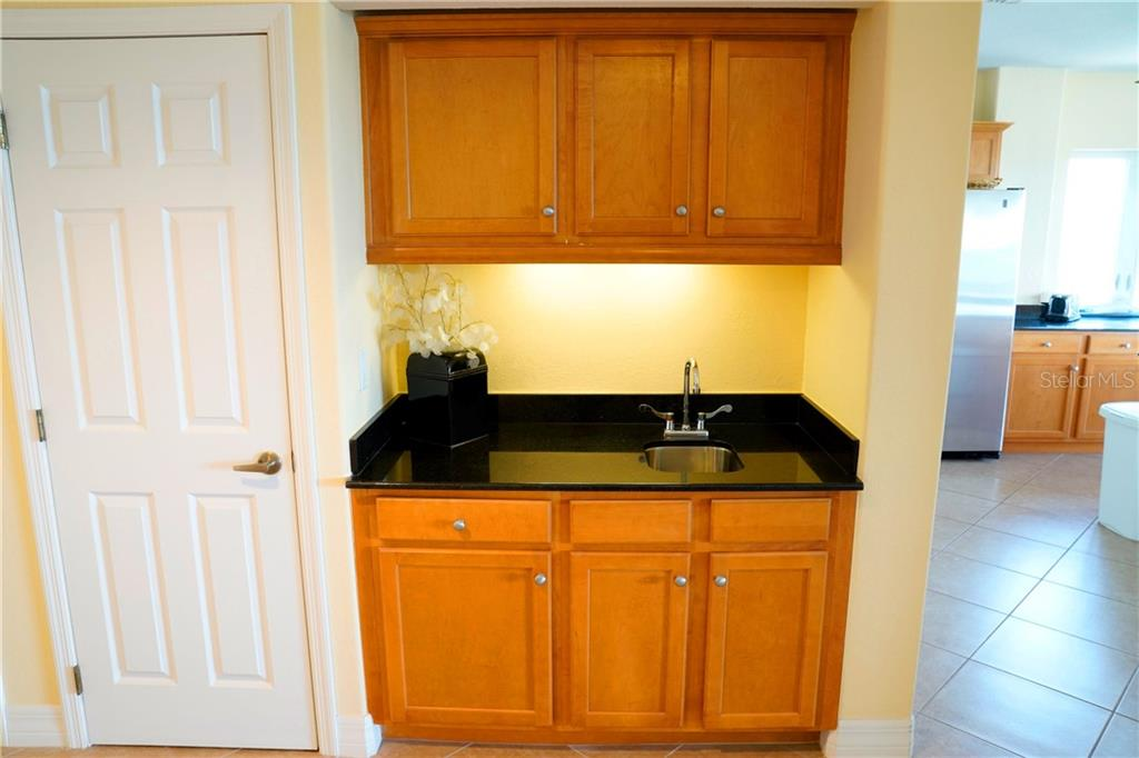 Another view of the entertainment wet bar.   Door to left is the 1/2 bath for guests. - Condo for sale at 2245 N Beach Rd #304, Englewood, FL 34223 - MLS Number is D6112346