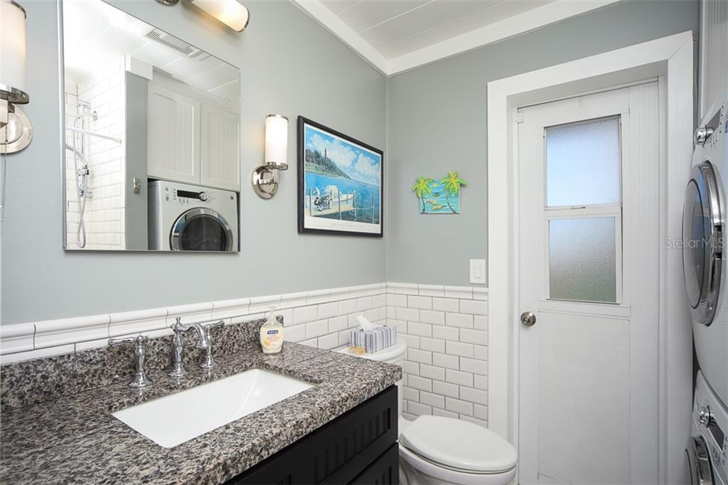 Bathroom with Carrara Marble Floor; Walk-In Shower with Subway Tile & Carrara Marble Floor; Vanity with Granite Counter; Washer & Dryer; Door leads to paved/grassy outside area and Outside Shower - Single Family Home for sale at 4074 N Beach Rd #Ctg4, Englewood, FL 34223 - MLS Number is D6114111