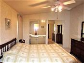 Master bedroom has vaulted ceiling, ceiling fan, walk in closet plus mirrored wall closet and Berber carpeted flooring. - Manufactured Home for sale at 1800 Englewood Rd #95, Englewood, FL 34223 - MLS Number is D6103776