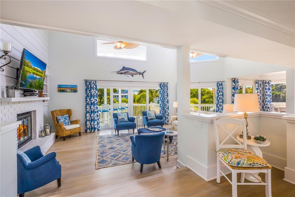 The family room is bright and open with multiple impact-rated sliding doors - Single Family Home for sale at 511 Loquat Dr, Anna Maria, FL 34216 - MLS Number is T3196169