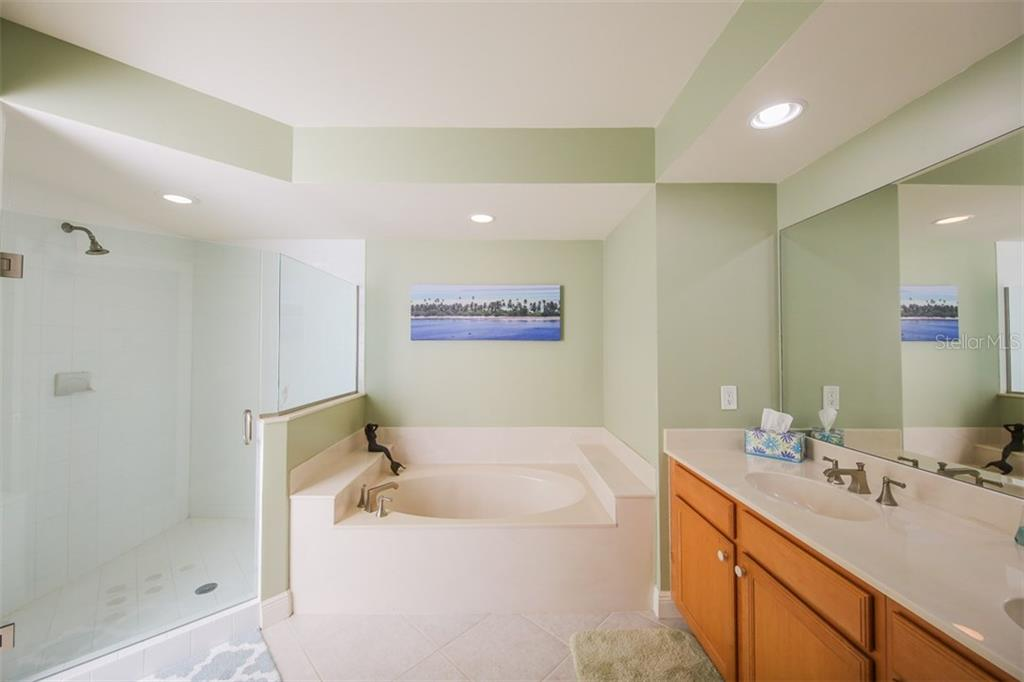 Master bath features a semi private commode, frameless glass shower, soaking tub and dual sinks with more honey color cabinetry. - Condo for sale at 3313 Sunset Key Cir #402, Punta Gorda, FL 33955 - MLS Number is C7236886