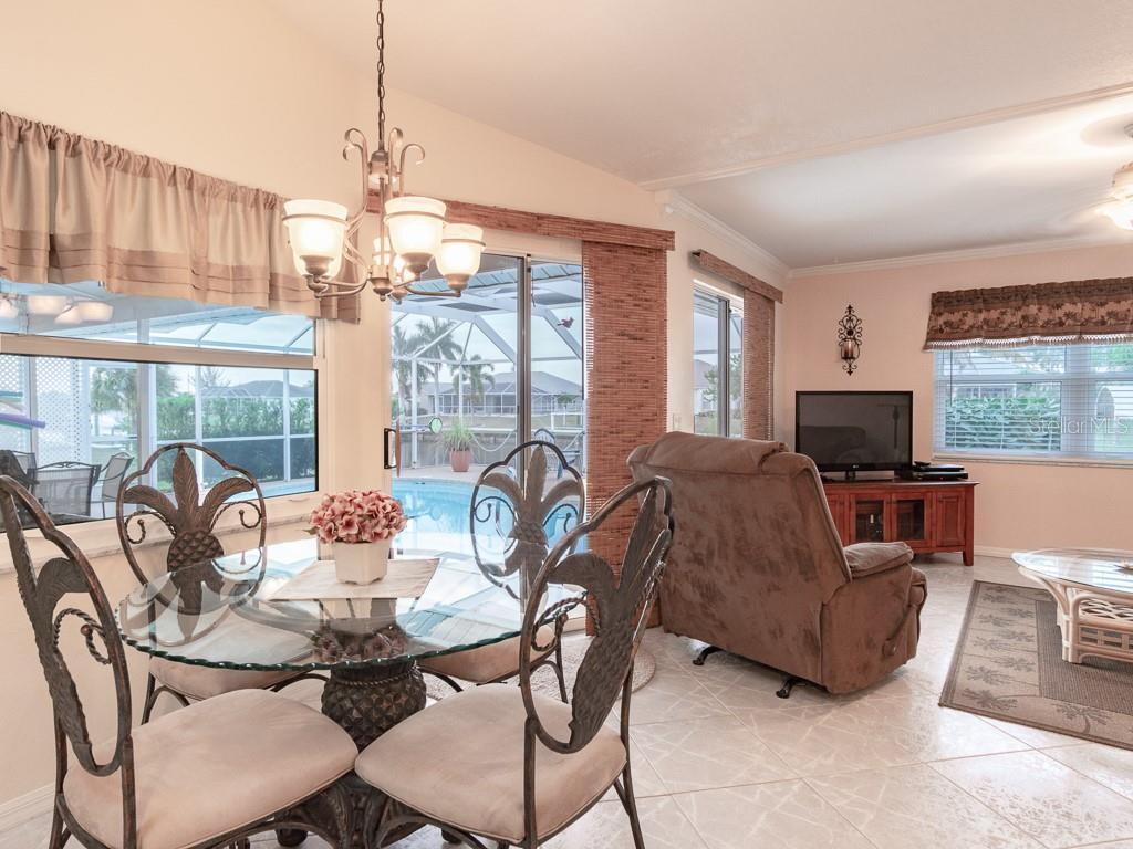 View from the kitchen to the dinette area and the family room - two more sliders out to the lanai that open the home up for entertainment inside and out - Single Family Home for sale at 15464 Avery Rd, Port Charlotte, FL 33981 - MLS Number is C7401914