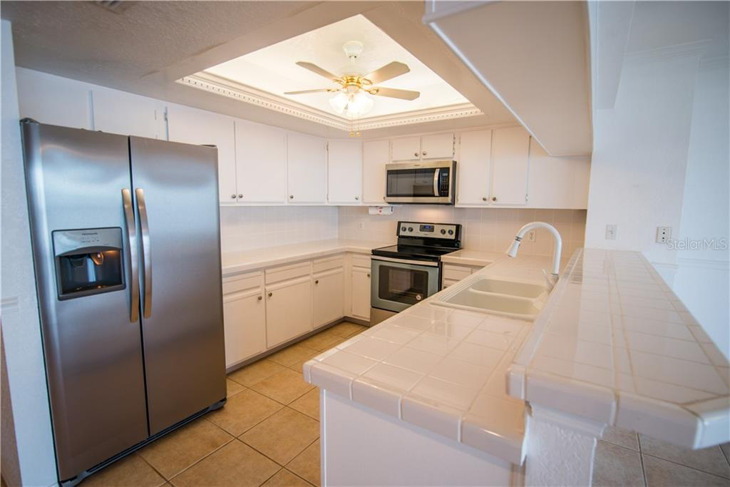 New Stainless Steel appliances and white tiled counters create a clean and bright look for your kitchen.  You'll love the tall breakfast counter. - Condo for sale at 1601 Park Beach Cir #112 / 2, Punta Gorda, FL 33950 - MLS Number is C7407435