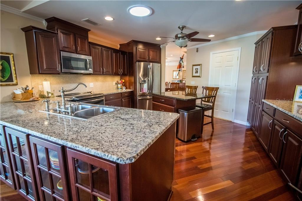 Rich granite countertops and stainless steel appliances complement the rich hardwood floors and cabinetry. - Single Family Home for sale at 1440 Appian Dr, Punta Gorda, FL 33950 - MLS Number is C7425399