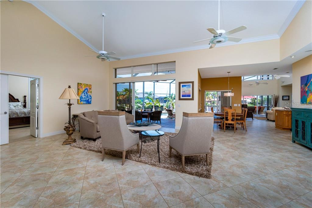 LIVING ROOM WITH CROWN MOLDING AND SLIDERS TO LANAI - Single Family Home for sale at 3537 Caya Largo Ct, Punta Gorda, FL 33950 - MLS Number is C7431664