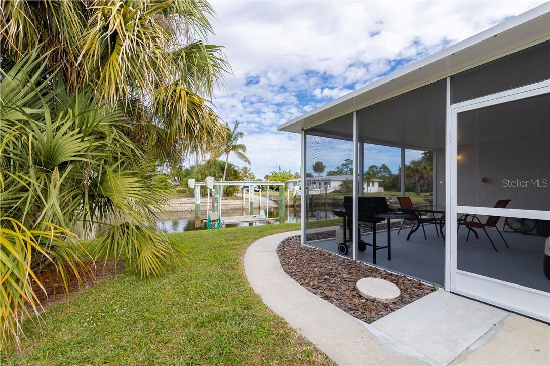 New lanai overlooking the canal, and 9,500 lb boat lift - Single Family Home for sale at 24368 Blackbeard Blvd, Punta Gorda, FL 33955 - MLS Number is C7436898