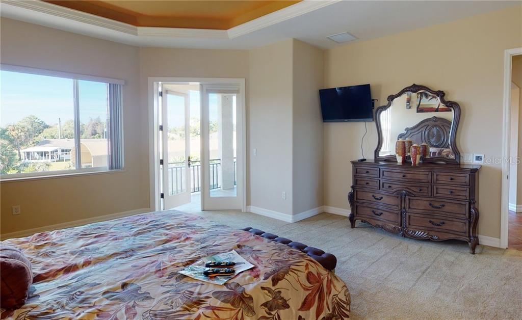 Master bedroom with doors out to the balcony. - Single Family Home for sale at 4245 Spire St, Port Charlotte, FL 33981 - MLS Number is C7437570