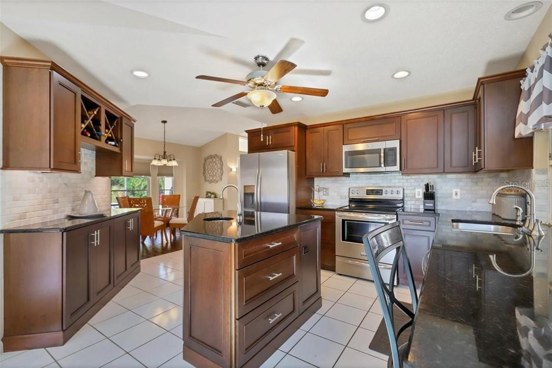 as you pass your dining room you'll delight in this remodeled kitchen, island boasts a sink and back sideboard has overhead wine storage and more cabinets, marble backsplash too.  Granite counter on right extends for breakfast
