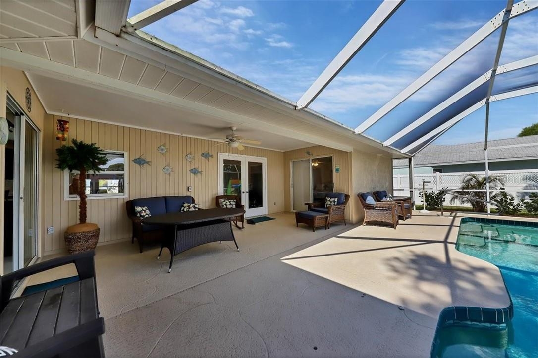 lanai is accessible from master suite sliders (right) French doors from living room, sliders from kitchen bar area and exit door in guest bath - Single Family Home for sale at 116 Mariner Ln, Rotonda West, FL 33947 - MLS Number is C7441260