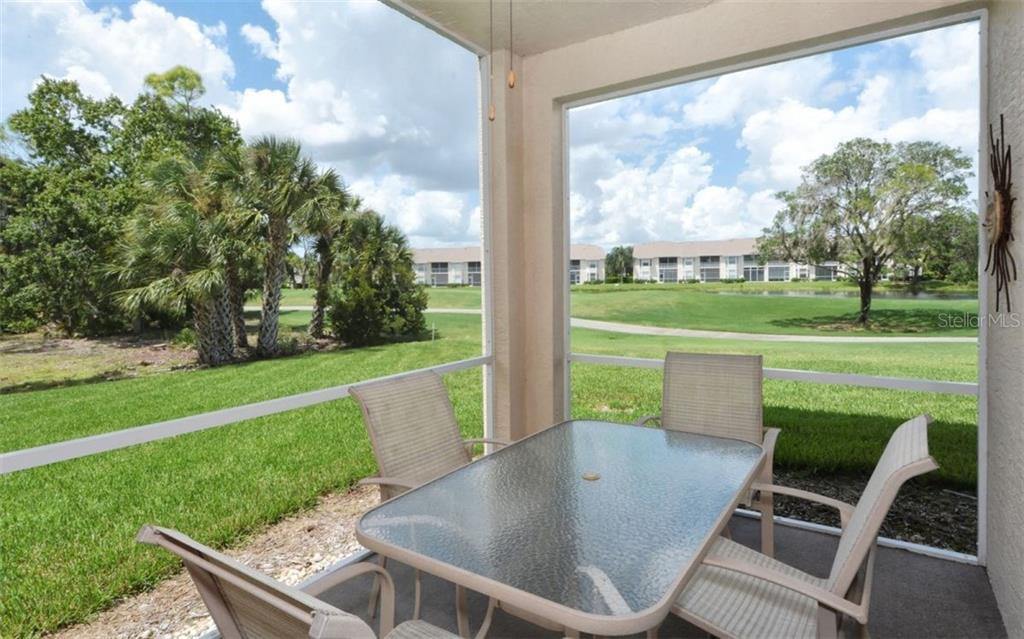 Lanai view of golf course, distant lake, and private tropical side area. - Condo for sale at 9630 Club South Cir #6103, Sarasota, FL 34238 - MLS Number is A4166105