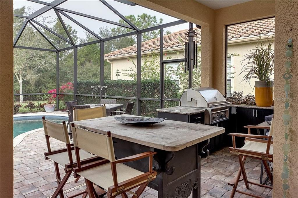 Outdoor kitchen with built in grill, cabinets and granite counters - Single Family Home for sale at 7254 Lake Forest Gln, Lakewood Ranch, FL 34202 - MLS Number is A4174107