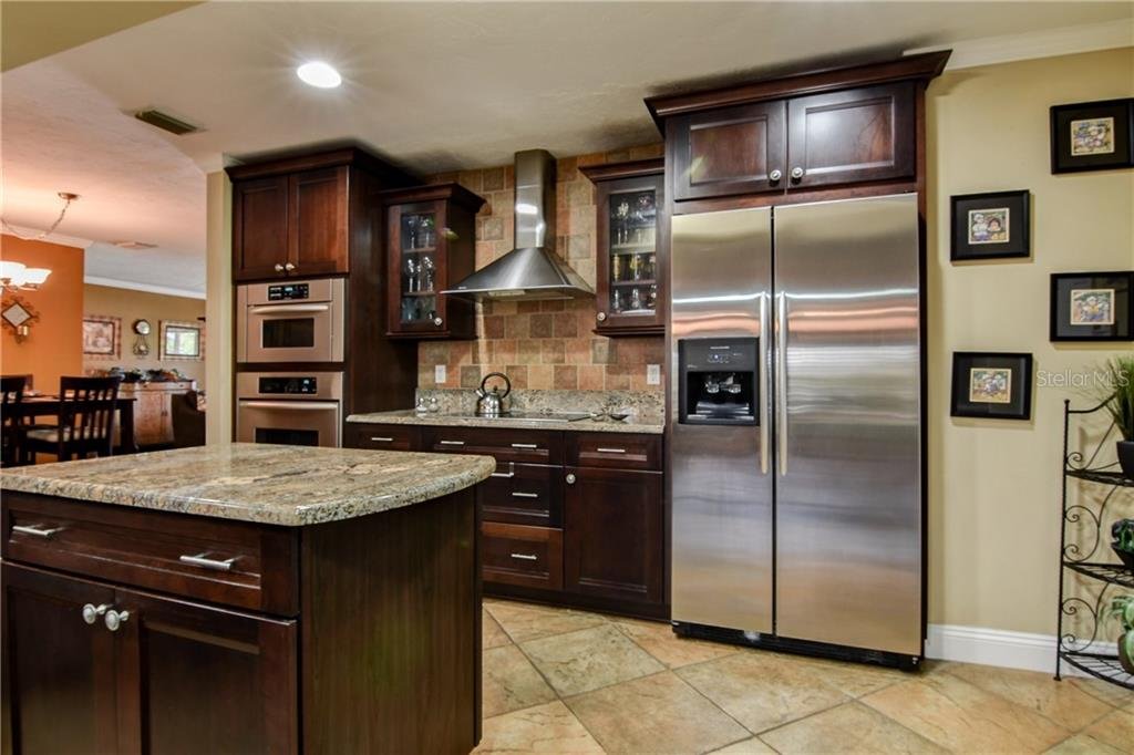 Luxury finishes continue with the dark cherry wood cabinets, granite counters,  stainless deep double sink and double dishwasher.  Your guests will gather at the expansive breakfast bar. - Single Family Home for sale at 8916 44th Avenue Dr W, Bradenton, FL 34210 - MLS Number is A4186449
