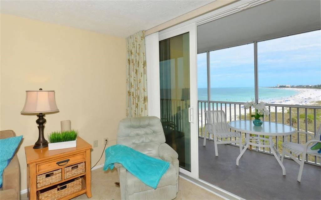 Living room with sliders to covered, screened terrace with gorgeous Gulf of Mexico and beach views - Condo for sale at 6300 Midnight Pass Rd #806, Sarasota, FL 34242 - MLS Number is A4189340