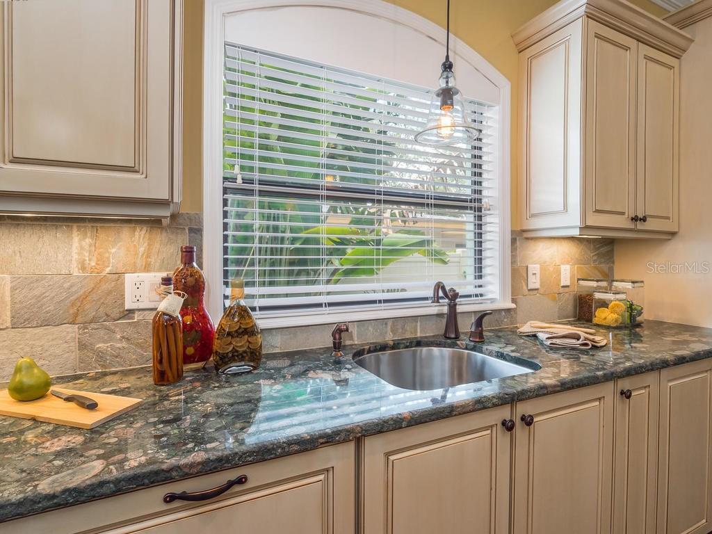 Stunning countertops, two sinks, window behind sink with hanging light fixture and stone backsplash. - Single Family Home for sale at 1884 Grove St, Sarasota, FL 34239 - MLS Number is A4189365