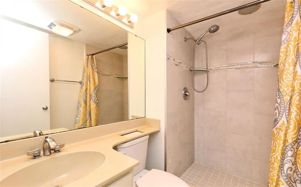 Guest bath with newly tiled walk-in shower - Condo for sale at 104 Woodland Pl #104, Osprey, FL 34229 - MLS Number is A4190676