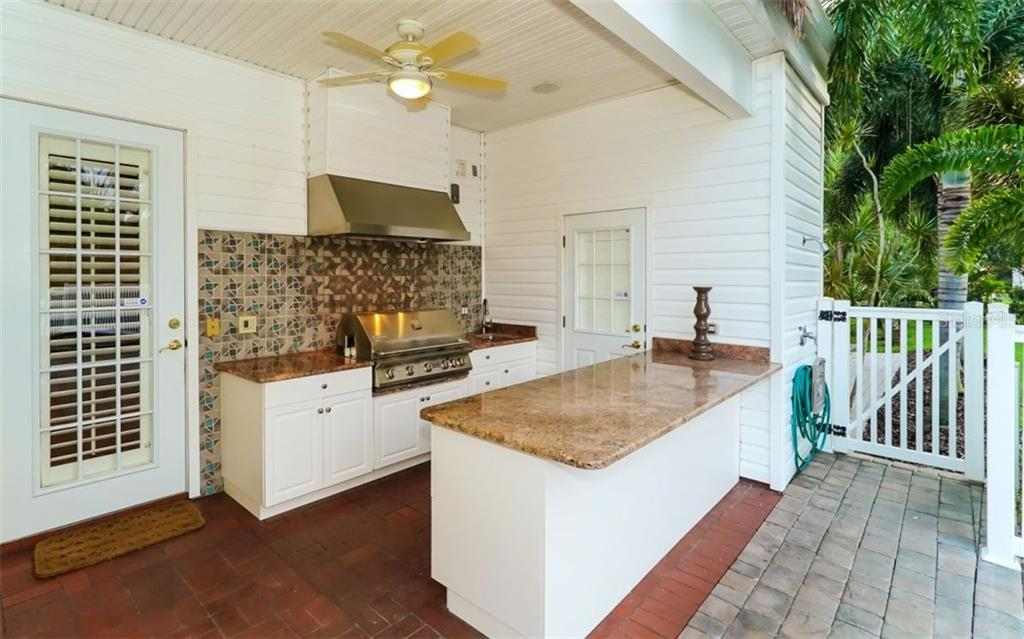 Outdoor kitchen with granite counter tops overlooking the pool area.  The half-bath is air-conditioned and holds remote control for lighting, waterfalls and spa. - Single Family Home for sale at 9818 9th Ave Nw, Bradenton, FL 34209 - MLS Number is A4194125