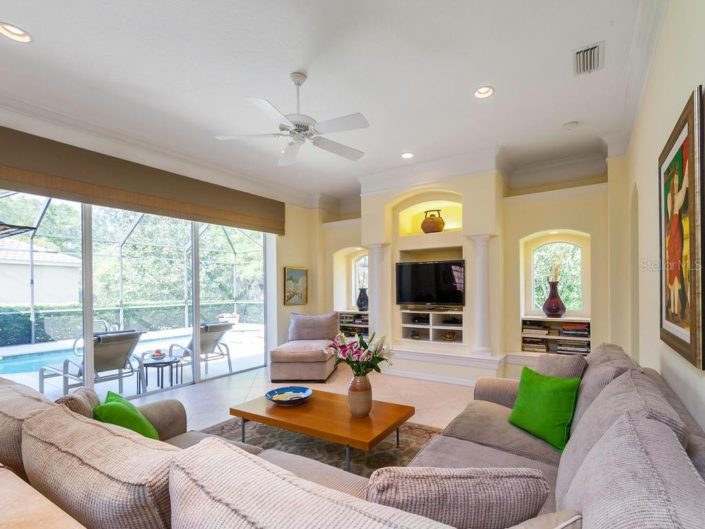 Large family room with sliding doors that pocket back to open up lanai. - Single Family Home for sale at 4887 Carrington Cir, Sarasota, FL 34243 - MLS Number is A4199511
