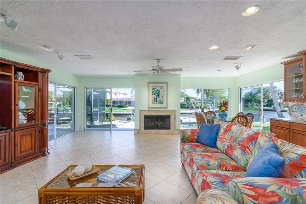 Family room with fireplace and four sliding doors to outside, with canal views - Single Family Home for sale at 5439 Azure Way, Sarasota, FL 34242 - MLS Number is A4203969