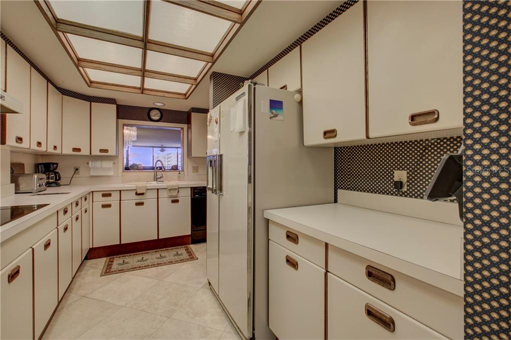Kitchen with pass through - Condo for sale at 5880 Midnight Pass Rd #610, Sarasota, FL 34242 - MLS Number is A4204670