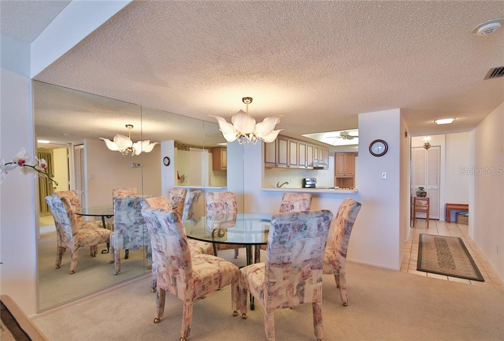 Looking from living room to dining room, kitchen and entry - Condo for sale at 5790 Midnight Pass Rd #704, Sarasota, FL 34242 - MLS Number is A4208095