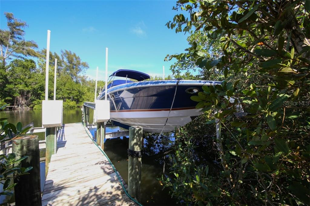 Private boat dock and 10,000lb boat lift.  30 ft boat in picture ( Available) - Single Family Home for sale at 455 Canal Rd, Sarasota, FL 34242 - MLS Number is A4209817