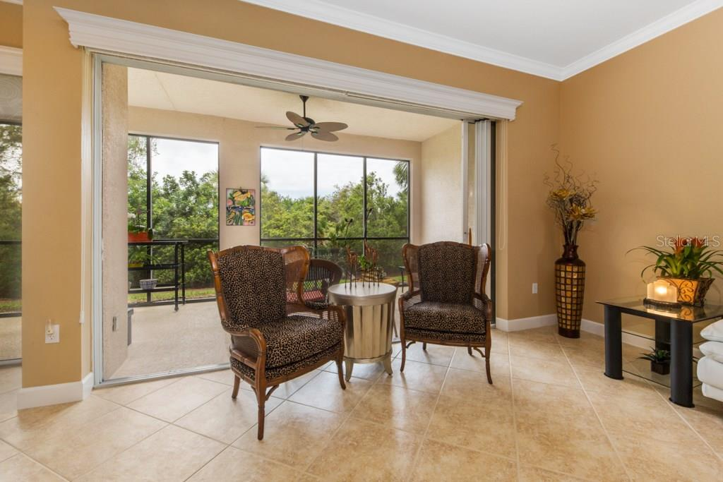 Large 8' high Sliding Glass Doors pocket away opening onto the Lanai. Custom blinds hide neatly away in the  Wood Valance above the sliders. - Condo for sale at 7504 Botanica Pkwy #101, Sarasota, FL 34238 - MLS Number is A4213208
