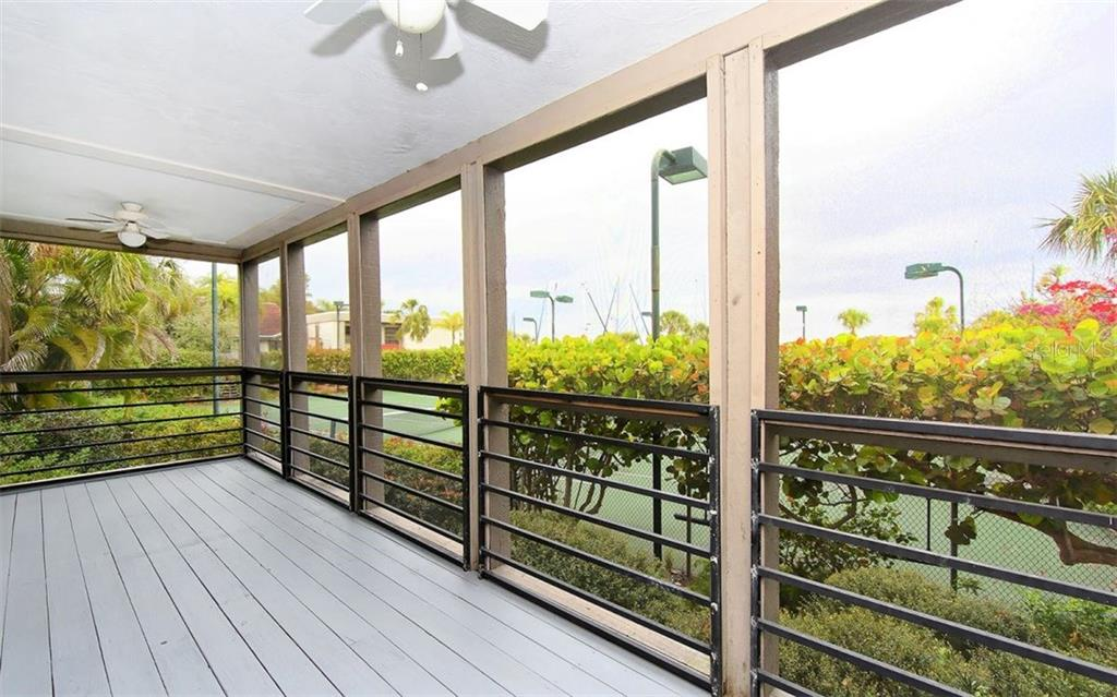 Screened porch overlooking tennis court and marina and Bay in the distance - Condo for sale at 3440 Gulf Of Mexico Dr #8, Longboat Key, FL 34228 - MLS Number is A4214047
