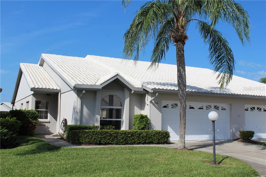 Front view of unit (1/2 of paired villa) with stately palm and lovely landscaping - Villa for sale at 5438 Kelly Dr #12, Sarasota, FL 34233 - MLS Number is A4400319