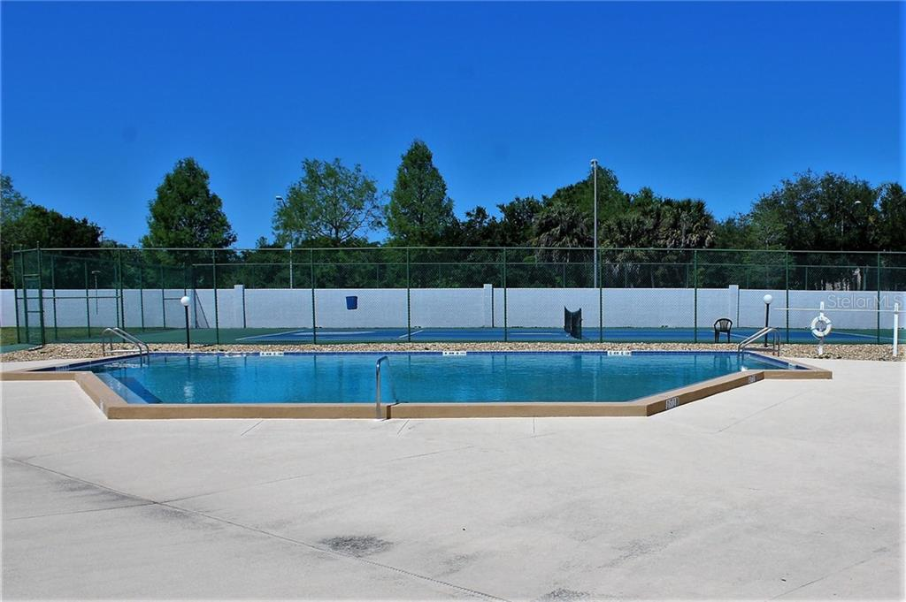 Here's another photo of the pool with the tennis court beyond. - Villa for sale at 5438 Kelly Dr #12, Sarasota, FL 34233 - MLS Number is A4400319