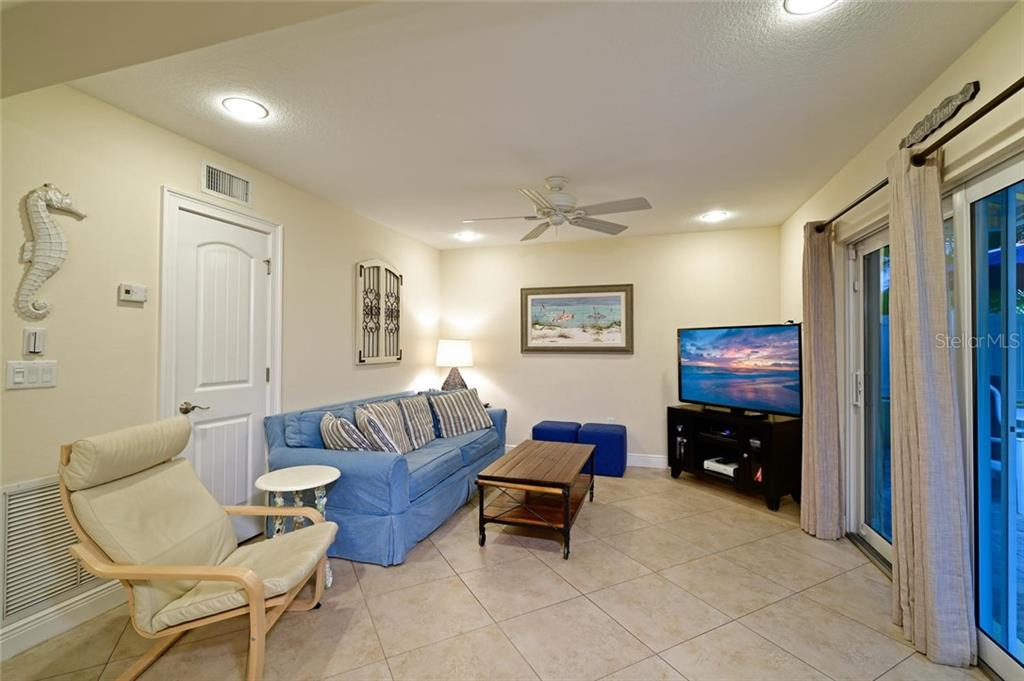 The cozy living room provides a comfortable place to watch TV and the pool is just outside. - Single Family Home for sale at 113 36th St, Holmes Beach, FL 34217 - MLS Number is A4407267