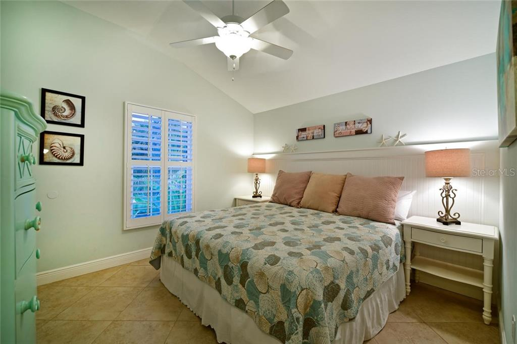 This bedroom has a view to a landscaped area through plantation shutters. - Single Family Home for sale at 113 36th St, Holmes Beach, FL 34217 - MLS Number is A4407267