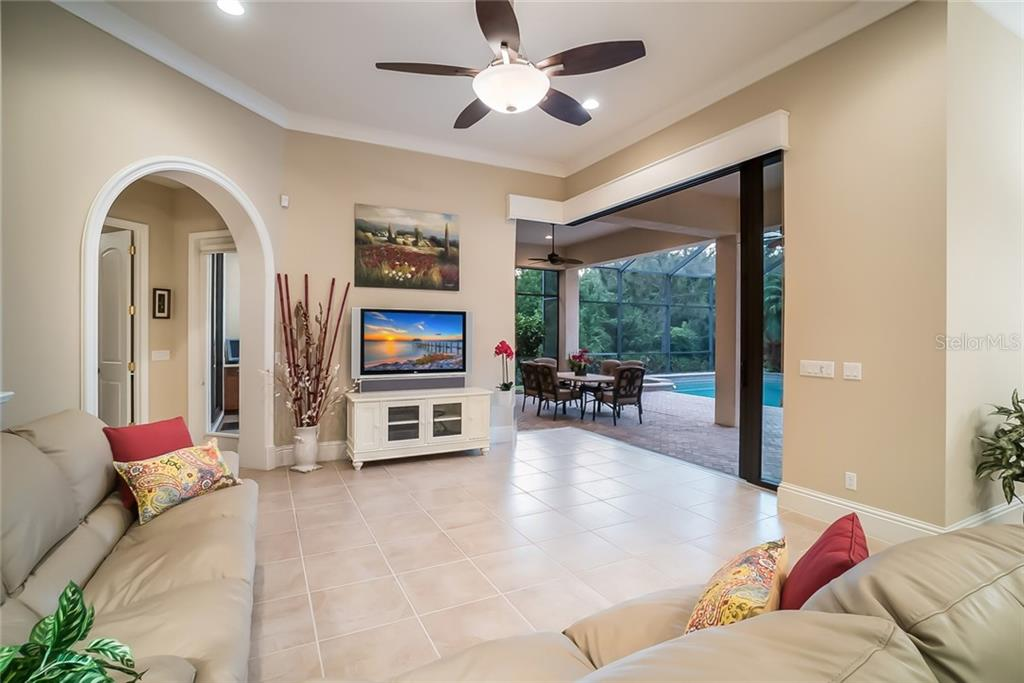 Family Room has zero-corner and pocket sliders to the outdoor covered entertaining spaces, with perfect views of the pool and preserve. - Single Family Home for sale at 13223 Palmers Creek Ter, Lakewood Ranch, FL 34202 - MLS Number is A4408290