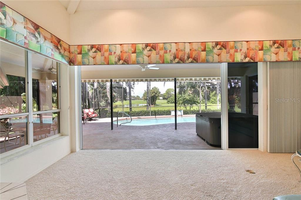 Sliding doors in the great room retract all the way to the right, providing seamless indoor-outdoor living. - Villa for sale at 7686 Calle Facil, Sarasota, FL 34238 - MLS Number is A4413755