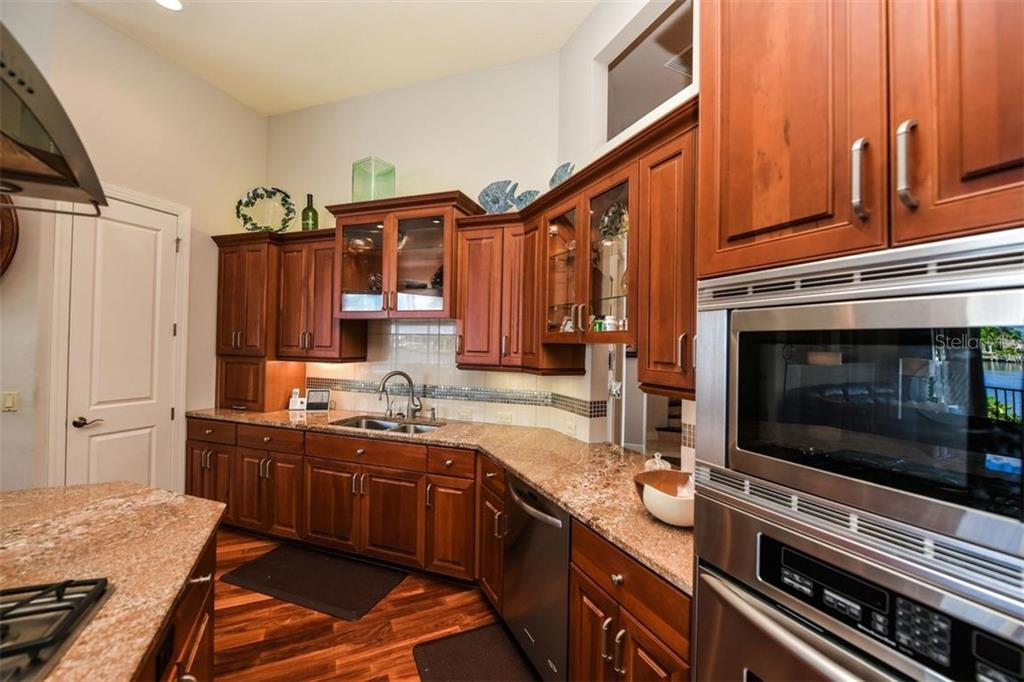 Lit upper cabinets. 9 ft island, walk in pantry loads of storage. - Single Family Home for sale at 1483 Tangier Way, Sarasota, FL 34239 - MLS Number is A4414757