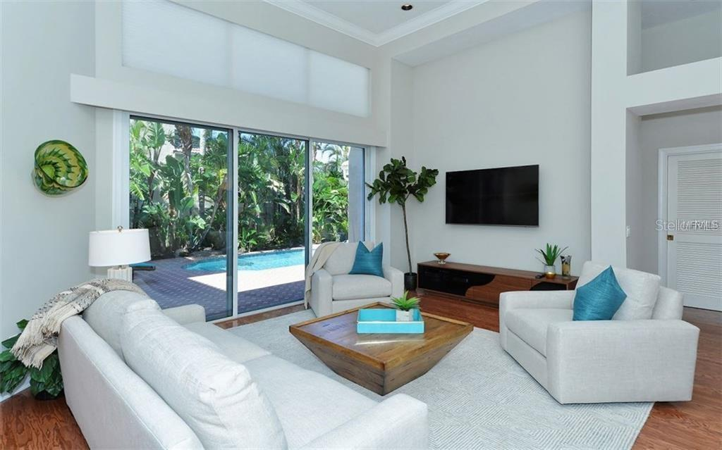 Opening the sliding doors allows you to enjoy the privacy of the courtyard pool from your family room - Single Family Home for sale at 3529 Fair Oaks Ln, Longboat Key, FL 34228 - MLS Number is A4414992