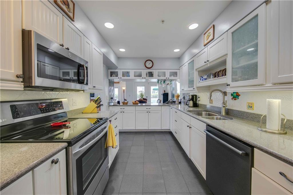 Looking through the kitchen to the dining area and out to the screened in deck overlooking the pool and canal - Single Family Home for sale at 660 Marbury Ln, Longboat Key, FL 34228 - MLS Number is A4415911