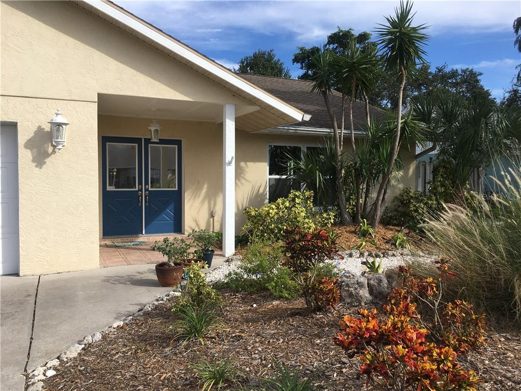 Welcoming double doors and tiled entrance with shell path and natural landscaping. - Single Family Home for sale at 1611 82nd St Nw, Bradenton, FL 34209 - MLS Number is A4417607