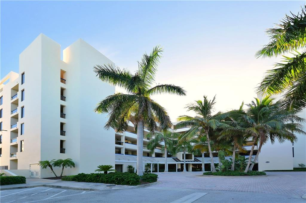 Exterior front of building with under building parking included with this unit. - Condo for sale at 1930 Harbourside Dr #117, Longboat Key, FL 34228 - MLS Number is A4420232