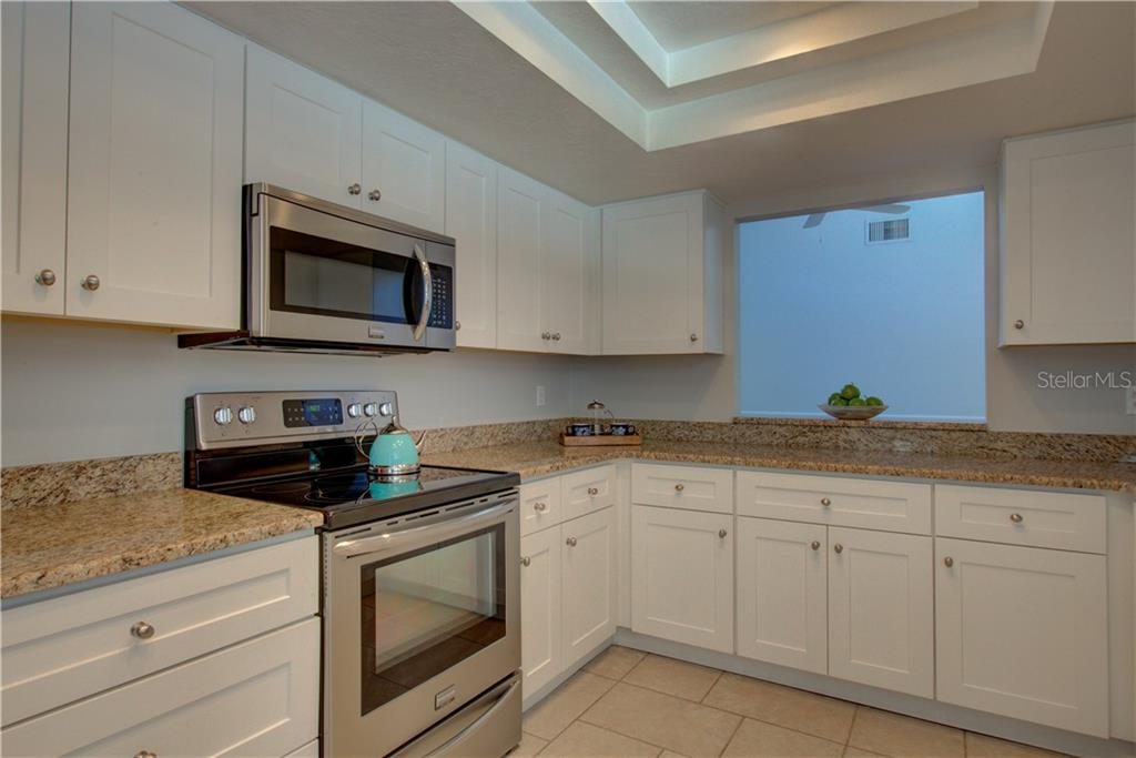 Kitchen with serving hatch through to the dining room - Single Family Home for sale at 5167 Kestral Park Ln, Sarasota, FL 34231 - MLS Number is A4421162