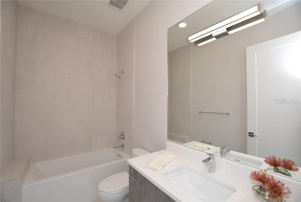 Bedroom 3 ensuite bath offers a tub/shower combination. - Condo for sale at 609 Golden Gate Pt #201, Sarasota, FL 34236 - MLS Number is A4422340