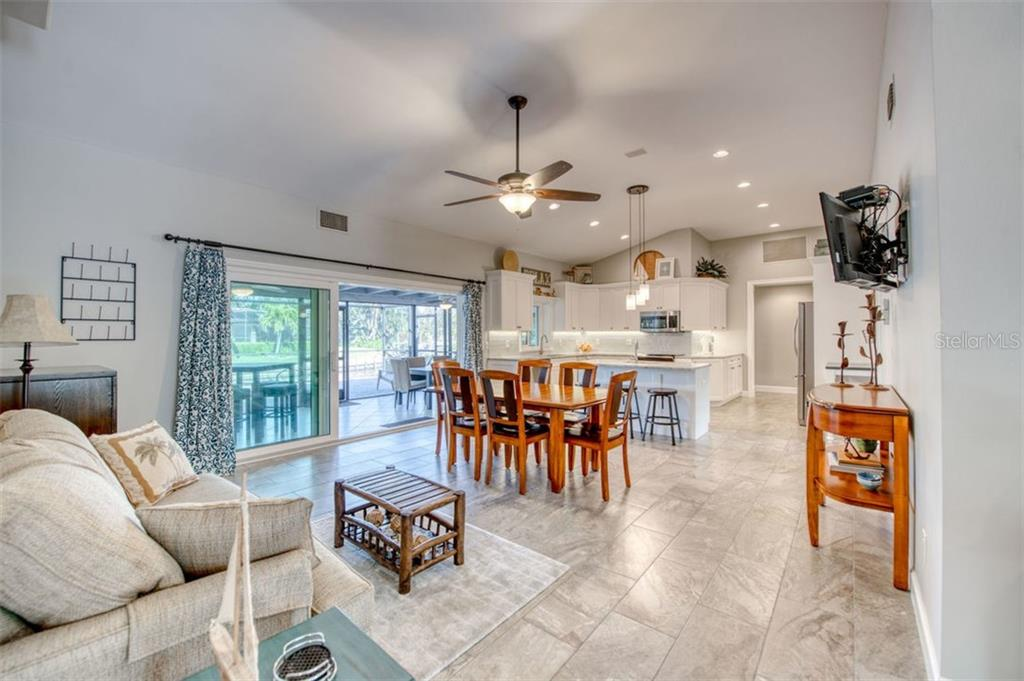 Family room, dining area and kitchen with sliders to pool - Single Family Home for sale at 5548 Shadow Lawn Dr, Sarasota, FL 34242 - MLS Number is A4423461