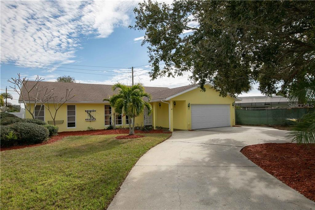 Once up the long private driveway, you're greeted with your lovely yellow home with the big front yard and a circular around the trees. - Single Family Home for sale at 6213 8th Avenue Dr W, Bradenton, FL 34209 - MLS Number is A4423560