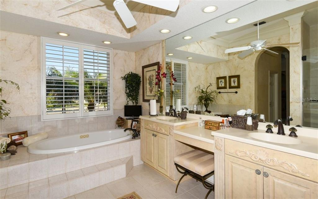 Large Master Bath with Corian Counters wood cabinets, Jacuzzi-Tub hand-painted walls - Single Family Home for sale at 561 Ketch Ln, Longboat Key, FL 34228 - MLS Number is A4426280