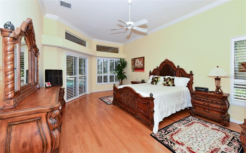 Large master bedroom with sliders that open to the pool/spa area - Single Family Home for sale at 7867 Estancia Way, Sarasota, FL 34238 - MLS Number is A4426528