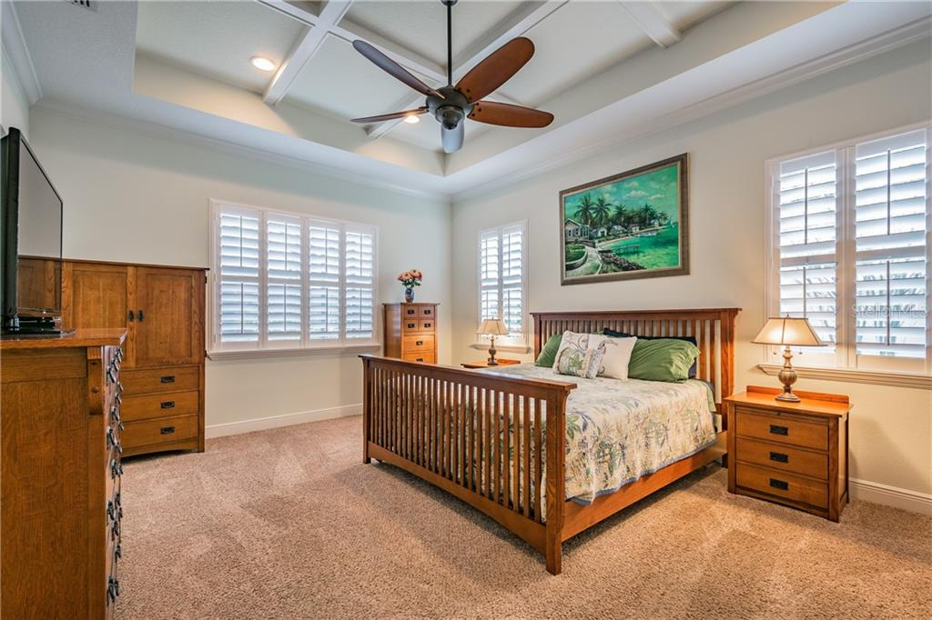 Spacious Master Bedroom with plantation shutter and coffered ceiling. - Single Family Home for sale at 595 Fore Dr, Bradenton, FL 34208 - MLS Number is A4428657